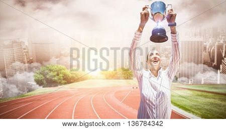 Successful businesswoman lifting a trophy against composite image of racetrack in city