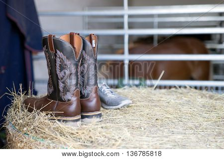 Riding boots in stables on straw bales