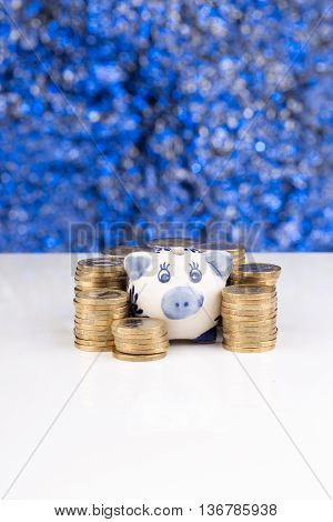 Piggy bank with a stack of coins and a blue blurry background