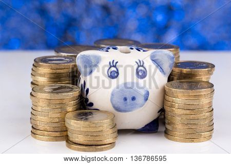 Piggy bank with a stack of coins and a blue blurry background up close