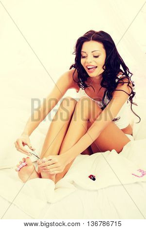 Attractive young woman cutting her feat nails