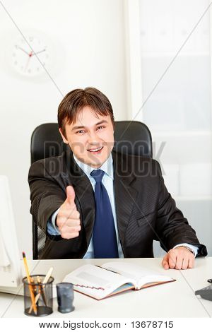 Pleased modern business man sitting at office desk and showing thumbs up gesture