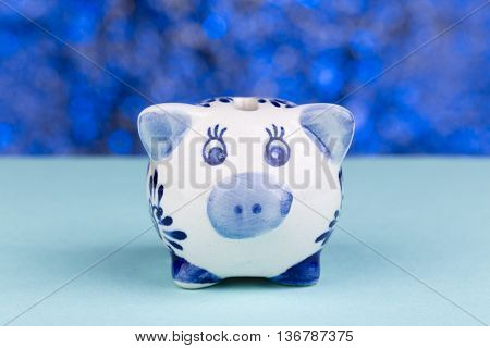 Close up of a piggy bank on a blue blackground with blur