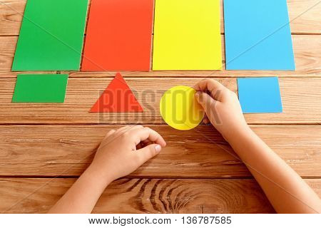 Child holds yellow cardboard circle in hands and puts on corresponding color card. Kid learns colors. Kit of colored cards for children of preschool age. Concept for learning in kindergarten, at home