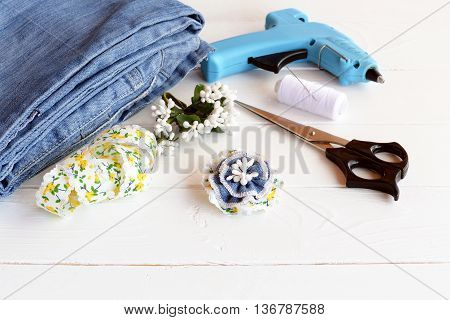 Stylish flower brooch using recycled old jeans. DIY home made denim accessory. Scissors, glue gun, lace, thread, needle, blue jeans on a wood table. Craft project for children