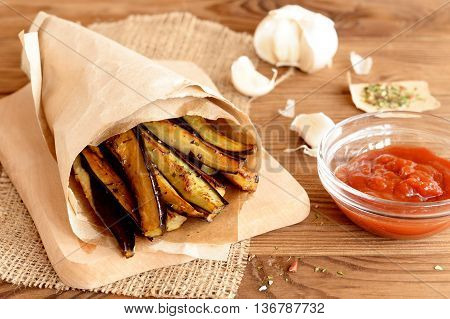 Crispy roasted eggplant slices with garlic and spices. Tomato sauce in glass bowl, spices, garlic on a wooden background. Easy cooking recipe of fried eggplant