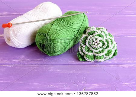Home made green and white crochet flower decorated with beads. Two skeins of cotton yarn and crochet hook on lilac wooden background. Easy knitting idea