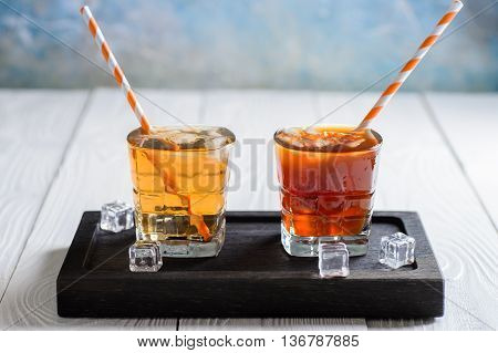 Ice Tea and Ice Coffee on a black wooden support with ice cubes