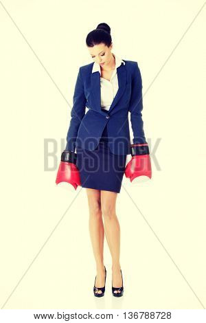 Defeated businesswoman in boxing gloves