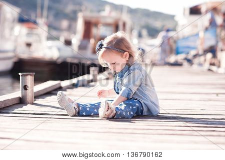 Cute baby girl 3-4 year old wearing stylish denim clothes sitting on wooden sea pier outdoors. Playful. Childhood. Summer season.