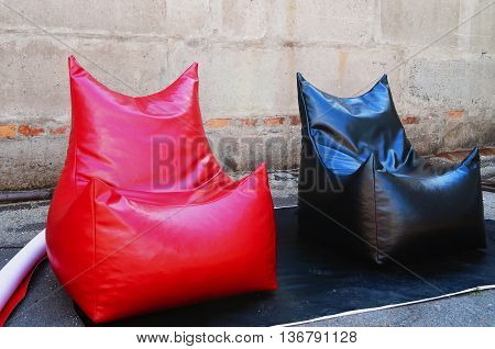 Beanbag of red and black color made ​​of shiny material on the background of gray wall