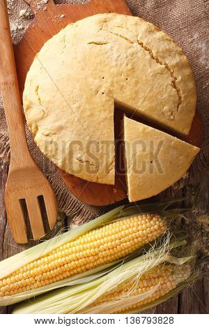 Round Loaf Of Corn Bread Close-up On A Wooden Board. Vertical Top View