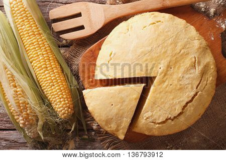 Round Loaf Of Corn Bread Close-up On A Wooden Board. Horizontal Top View