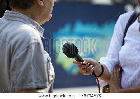 Media interview. Reporter holding a microphone conducting an TV or radio interview.
