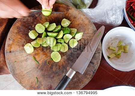 Chef chopping lemon on a wooden chopping board