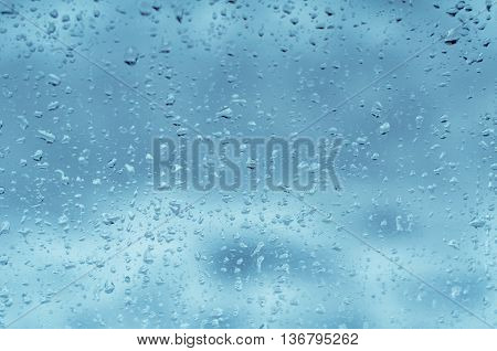 Background of water rain drops on glass, toned blue