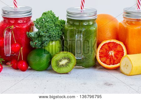 Colorful smoothy drinks in glass jars with igredients close up