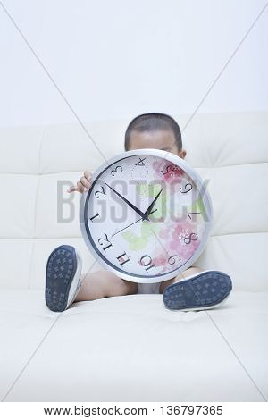 Cute Chinese Baby Boy Playing A Clock In Sofa