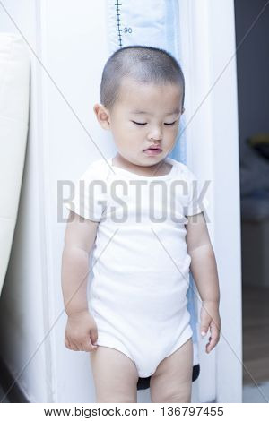 Cute Chinese Baby Boy Measuring His Height Indoors