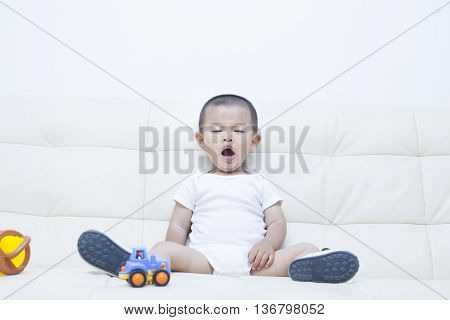 Cute Chinese Baby Yawning In Sofa