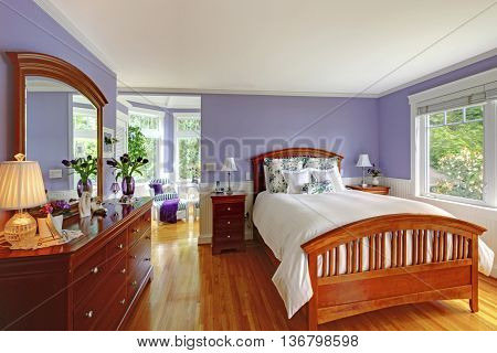 Adorable Bright Bedroom Interior With Purple Walls And Brown Furniture.