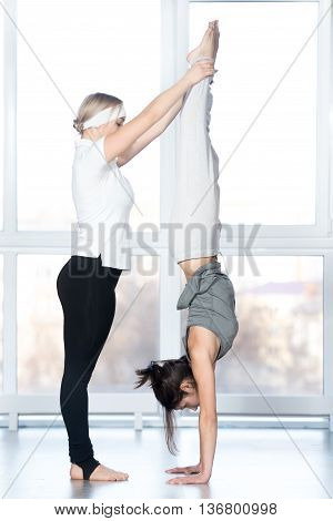 Fitness practice instructor helping young beautiful student female to do handstand in class Adho Mukha Vrksasana Downward facing Tree Pose two fit people working out in sports club full length