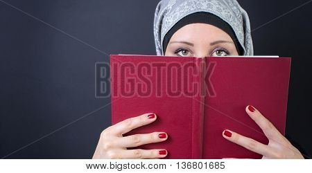 Young muslim woman in hijab holding a book