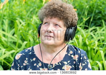 Curly woman listening to music through headphones