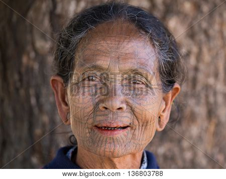 MRAUK-U MYANMAR - JANUARY 27 2016: The portrait of Chin woman with spider tattoo. Chin people also known as the Kukis are a number of Tibeto Burman tribal people.