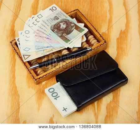 Polish money pen wallet and abacus on the table