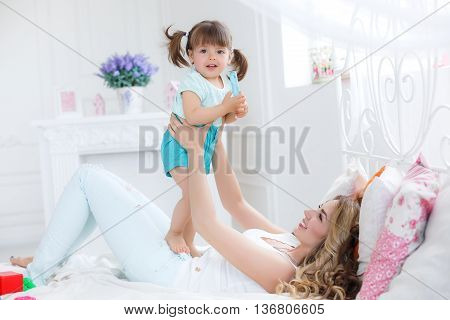 Happy young mother,blonde with long curly hair playing with his little daughter, a brunette, spend time in bright bedroom on a white bed,both dressed in white panties and white tops,having fun and smiling