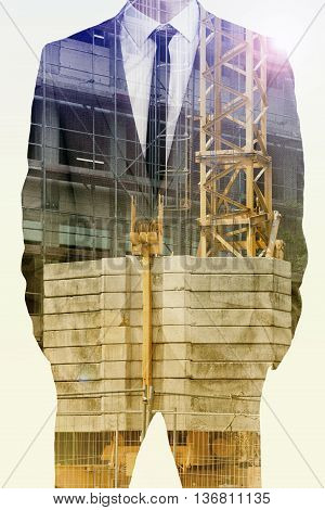 double exposure of businessman and construction site with crane