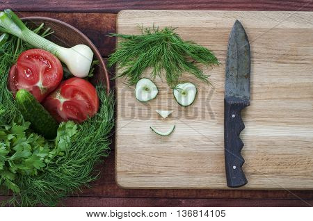 Tomato cucumber and green salad on the plate grass beside funny faces from slices of vegetables