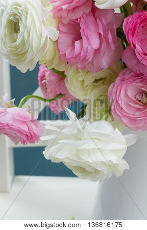 Pink and white ranunculus flowers bouquet in vase close up