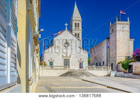 Parish church and clock tower Leroy are marble landmarks in island of Brac, town Supetar, Croatia. /