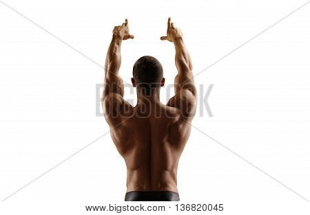 Muscular man standing with his back lifting his hands up. Isolate.