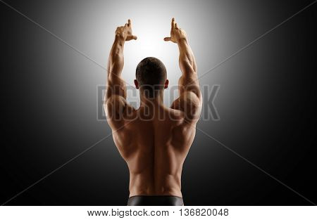 Muscular man standing with his back lifting his hands up. Black background.