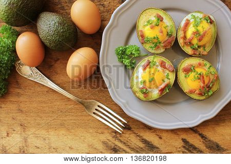 Avocado Egg Boats with bacon on wooden table