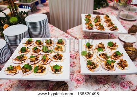 Spicy scallops on white plate in party