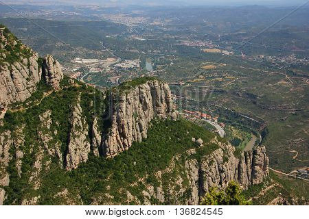 on the slopes of mount Montserrat, smooth, flowing mountains, little vegetation, and the bottom land of Spain, lots of greenery, road, river, settlement