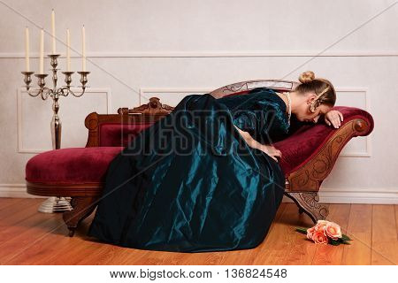 victorian woman crying on couch with roses on floor