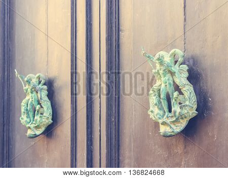 A Pair of Old Metal Poseidon Shaped Knockers on Wooden Door in Mdina Malta. Blue and yellow coloring filter used