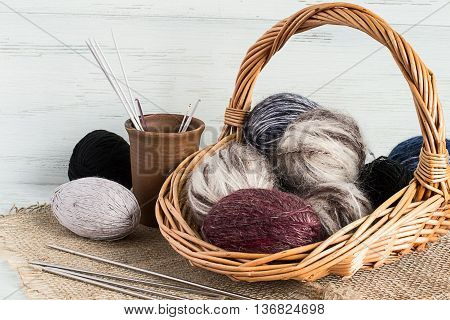 Balls wool yarn in a wicker basket and knitting needles in a clay cup on sackcloth.
