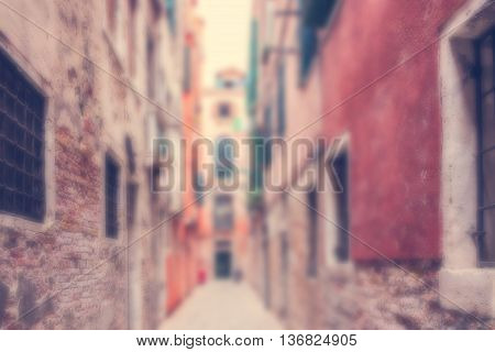 Defocused Background with old medieval houses along narrow street of Venice Italy