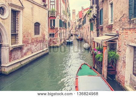 Defocused Background with old medieval houses along canal of Venice Italy. Part of the boat in foreground. Retro vintage grunge style filter used