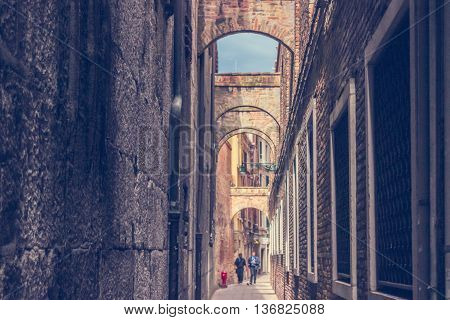 Background with two Men walking down the narrow Street