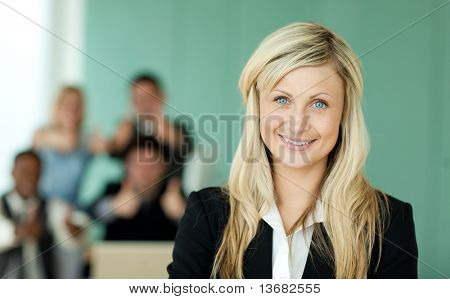 Businesswoman in front of her team in an office with a green background