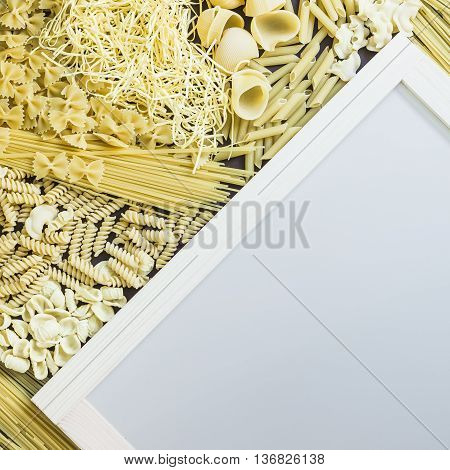 Mixed dried pasta selection surrounding white board with wooden frame for your text. Square composition. Top view shot