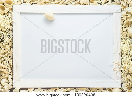 Mixed dried pasta selection surrounding white board with wooden frame for your text. Top view shot