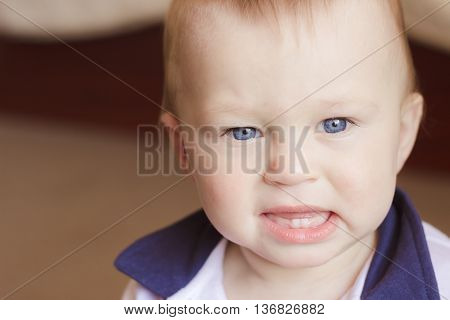 Angry boy with two teeth is about to cry. Baby health concept. Selective focus